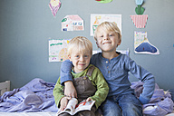 Portrait of two little brothers sitting on bed of children's room - RBF004247
