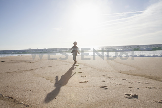 Back view of boy running on the beach at twilight - RBF004259