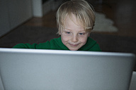 Portrait of smiling blond boy looking at computer - RBF004265