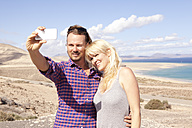 Spain, Fuerteventura, Jandia, couple taking selfie at the coast - MFRF000592