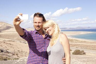Spain, Fuerteventura, Jandia, couple taking selfie at the coast - MFRF000592