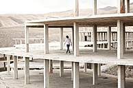 Spain, Fuerteventura, Jandia, architect walking in building shell - MFRF000613