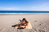 Spain, Tenerife, young woman reading book on the beach - SIPF000329
