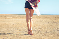 Spain, Tenerife, young woman walking in sand - SIPF000335