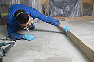 Worker checking the level of the concrete floor - RAEF001027