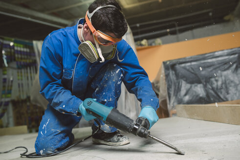 Worker treating the cement floor with a jackhammer - RAEF001033