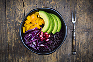 Lunch bowl with black rice, avocado, yellow bell pepper, red cabbage and pomegranate seed on wood - LVF004728