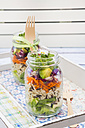 Springtime salad in glasses, lettuce hearts, radicchio, avocado, carrot, zucchini, wild rice and cress, daisy - LVF004734