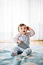 Portrait of baby girl sitting on blanket holding smartphone - BRF001302