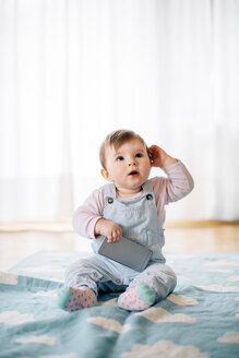 Portrait of baby girl sitting on blanket holding smartphone - BRF001302