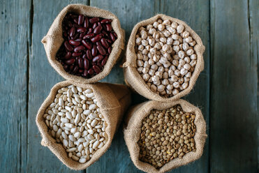 Four sacks of dried brown lentils, chickpeas and red and white beans on wood - KIJF000309