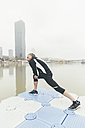 Austria, Vienna, jogger doing stretching exercise on Danube Island - AIF000313