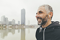 Austria, Vienna, portrait of smiling jogger with earphones in front of Donau City - AIF000319