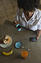 Top view of young woman with espresso cup looking at her phablet - MAUF000424