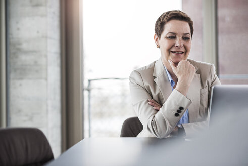 Smiling businesswoman at desk looking at laptop - UUF006760