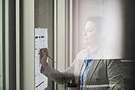 Businesswoman with construction plan at the window - UUF006766
