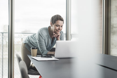 Businesswoman looking at laptop in office - UUF006799