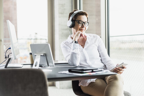 Businesswoman with cell phone and headphones in office - UUF006820