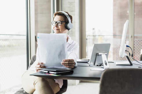 Businesswoman with headphones and document in office - UUF006823