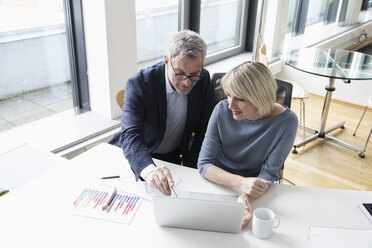Businessman and woman working together in office using laptop - RBF004277