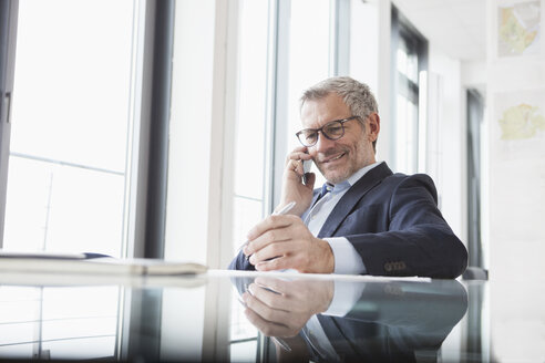 Successful businessman in his office talking on the phone - RBF004298