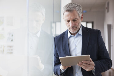 Successful businessman standing in his office holding digital tablet - RBF004319