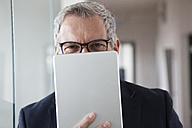 Successful businessman standing in his office holding digital tablet - RBF004325