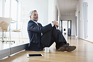 Successful businessman sitting on floor taking a break - RBF004328