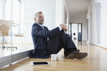 Successful businessman sitting on floor taking a break - RBF004328
