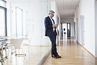 Successful businessman using in his office lookking at smart phone - RBF004331