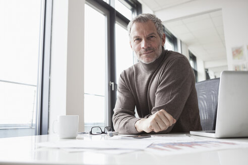 Mature man sitting in office using laptop - RBF004340
