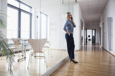 Businesswoman standing in office talking on the phone - RBF004373
