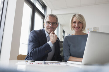 Businessman and woman working together in office using laptop - RBF004379