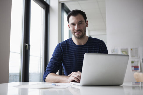 Young man sitting in office using laptop - RBF004406