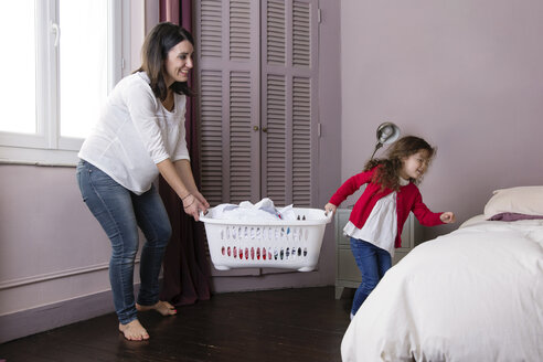 Mother and little daughter carrying  laundry basket together - LITF000251