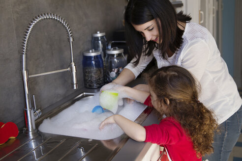 Mother and little daughter washing dishes together - LITF000254