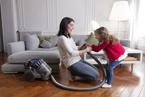 Mother and little daughter having fun with vacuum cleaner in the living room - LITF000257