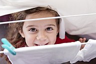 Portrait of little girl standing under a drying rack - LITF000260