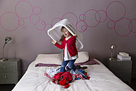 Little girl playing on parents' bed with laundry basket - LITF000263