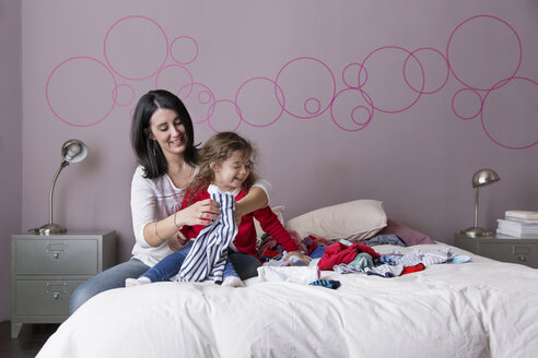 Mother and little daughter folding laundry together on the parents' bed - LITF000266