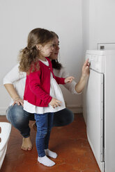 Mother explaining her little daughter operating of tumble dryer - LITF000272