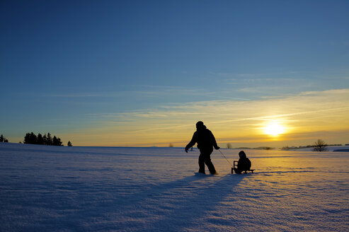 Mother and daughter sledging at sunset - LHF000498