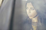 Portrait of young woman sitting in a car looking through window - ABZF000333