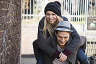 Young man giving his girlfriend a piggyback ride - LFOF000221