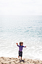 Happy little boy dancing on the beach at seafront - VABF000434