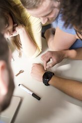 Creative professionals in office looking at smartwatch - FKF001785
