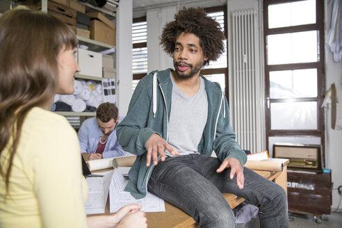 Three creative professionals talking in office - FKF001791