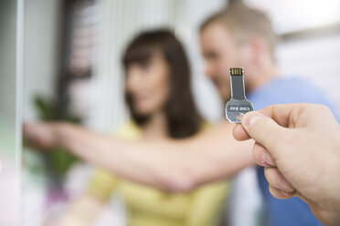 Hand holding an usb keychain in office - FKF001815