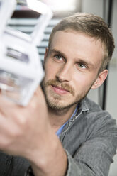 Young man examining architectural model - FKF001821