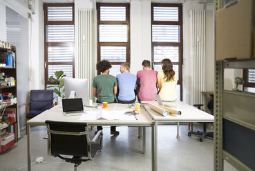 Team of creative professionals sitting on desk in office - FKF001824